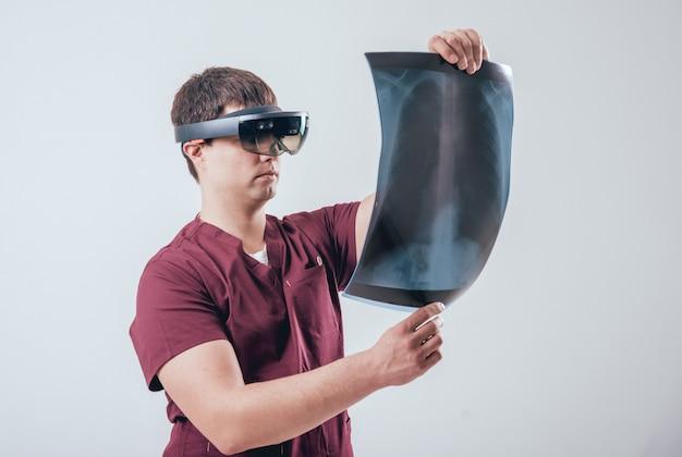 Der arzt verwendet eine augmented-reality-brille, um den röntgenfilm mit dem menschlichen skelett zu untersuchen
