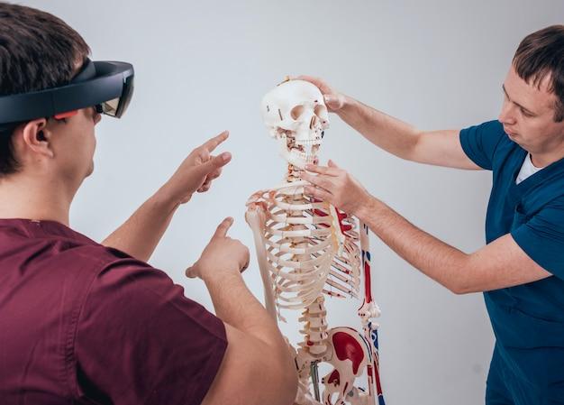 Der arzt verwendet eine augmented-reality-brille und ein menschliches skelett, um die schüler zu unterrichten