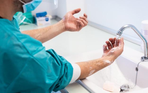 Der arzt wäscht sich die hände, bevor er in einer privatklinik operiert