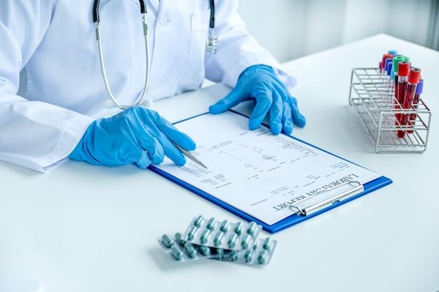 Der arzt zeichnet die blutuntersuchung und die medikamentenverwendung des medizinischen untersuchungskonzepts des patienten auf