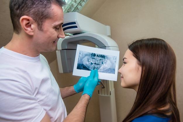 Der arzt zeigt dem patienten ein röntgenbild. computerdiagnose. zahntomographie