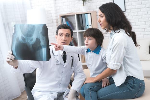 Der arzt zeigt eine röntgenaufnahme des jungen.