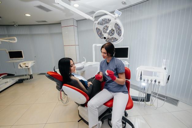 Der arzt zeigt einen abguss des kiefers des patienten