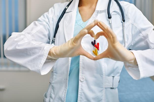 Der arzt zeigt herzsimbols durch die in form eines herzens gefalteten hände mit medizinischem versorgungskonzept, medizin im krankenhaus, kardiologie.