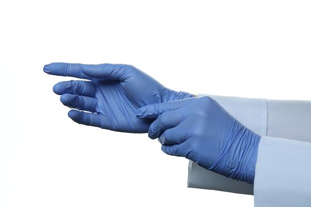 Der arzt zieht medizinische handschuhe an, die auf weiß isoliert sind