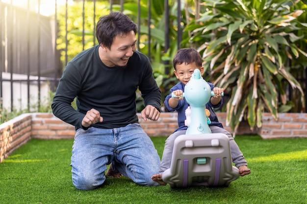 Der asiatische alleinerziehende vater mit seinem sohn spielt zusammen, wenn er auf dem rasen vor dem selbstlernen lebt