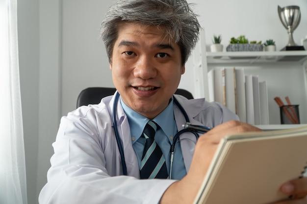 Der asiatische arzt ist online mit einem patienten in der internetanwendung zu besuch und notiert die symptome