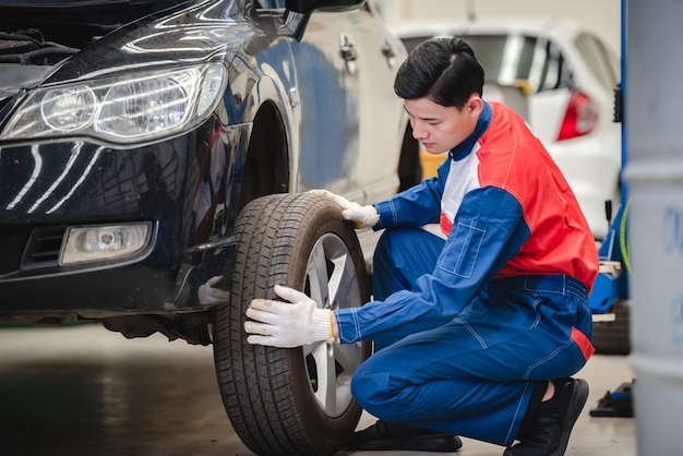 Der asiatische automechaniker entfernt das rad und überprüft die bremsen und die federung im autoservice mit einem gabelstapler. reparatur- und wartungszentrum