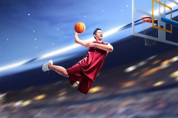 Der asiatische basketballspieler springt in die luft, während der ball versucht, ein tor zu erzielen