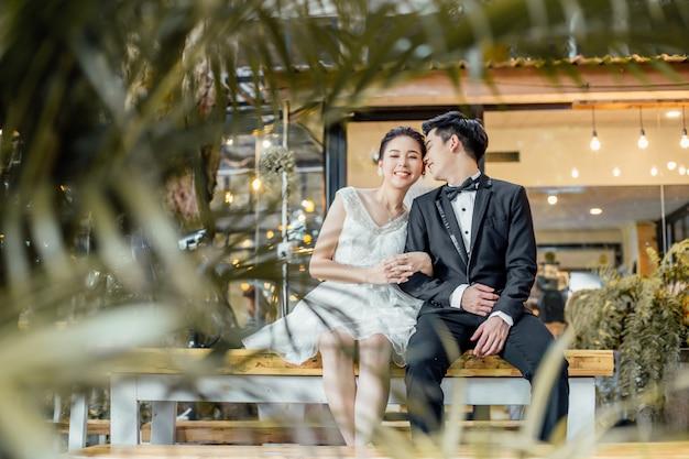 Der asiatische bräutigam, der nahe bei asiatischer braut sitzt und etwas neben ihrem ohr flüstert, gibt ihr ein lächeln.