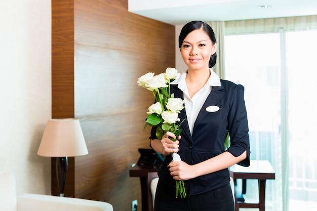 Der asiatische chinesische hotelmanager heißt ankommende vip-gäste willkommen