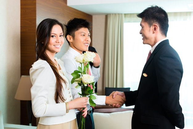 Der asiatische chinesische hotelmanager heißt vip-gäste willkommen