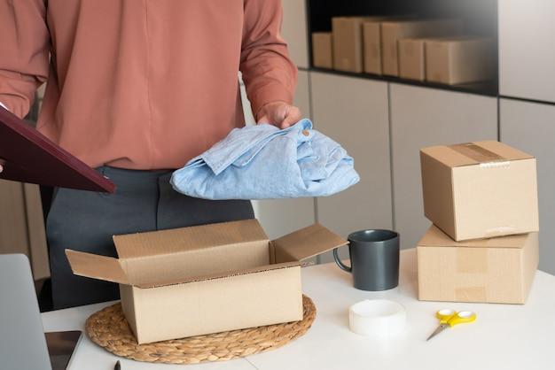 Der asiatische geschäftsinhaber, der zu hause mit der verpackungsschachtel seines online-shops arbeitet, bereitet sich auf die lieferung von produkten vor