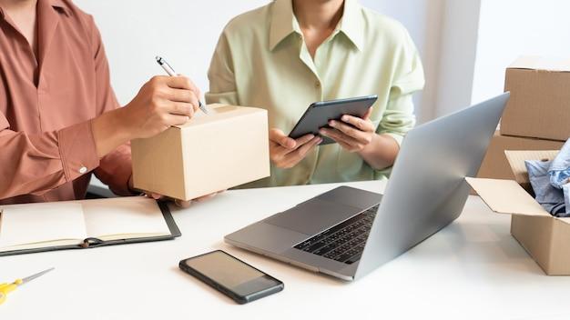 Der asiatische geschäftspaarbesitzer, der zu hause mit der verpackungsbox ihres online-geschäfts arbeitet, bereitet sich auf die lieferung vor