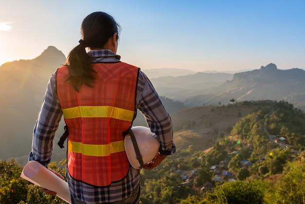 Der asiatische ingenieur trägt einen weißen helm und eine blaupause und schaut auf den berg, in dem sich auf der spitze des hügels ein dorf befindet