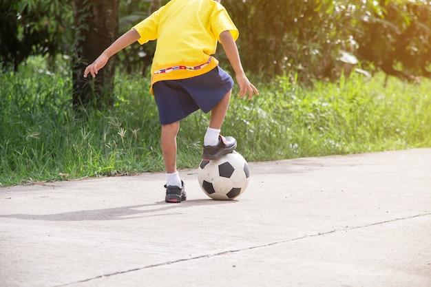 Der asiatische junge, der alten fußball auf straße spielt, spielen fußball für übung am abend