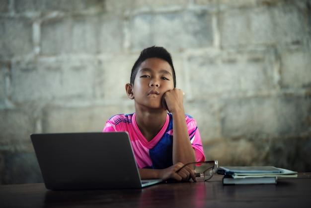 Der asiatische junge, der auf dem tisch laptop verwendet, kommen zu shcool zurück