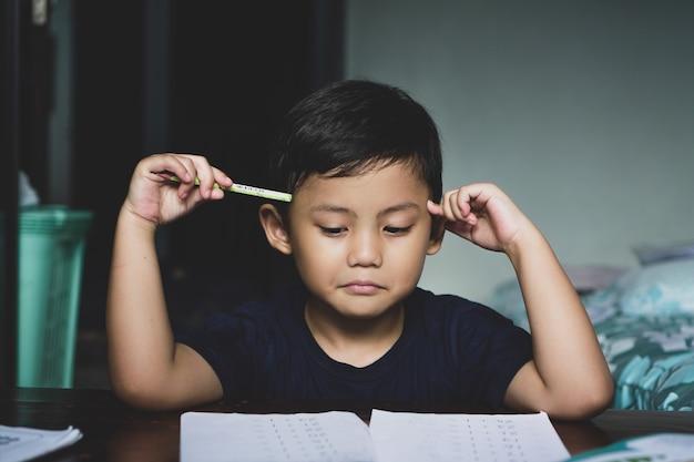 Der asiatische junge, der hinter dem schreibtisch saß, schien sich auf sein studium zu konzentrieren