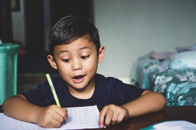 Der asiatische junge, der hinter dem schreibtisch saß, schrieb etwas mit einem aufgeregten gesichtsausdruck