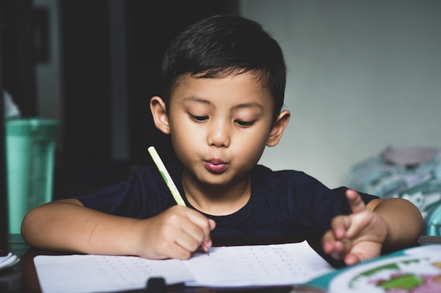 Der asiatische junge, der hinter dem schreibtisch saß, schrieb etwas mit einem selbstbewussten und aufgeregten ausdruck