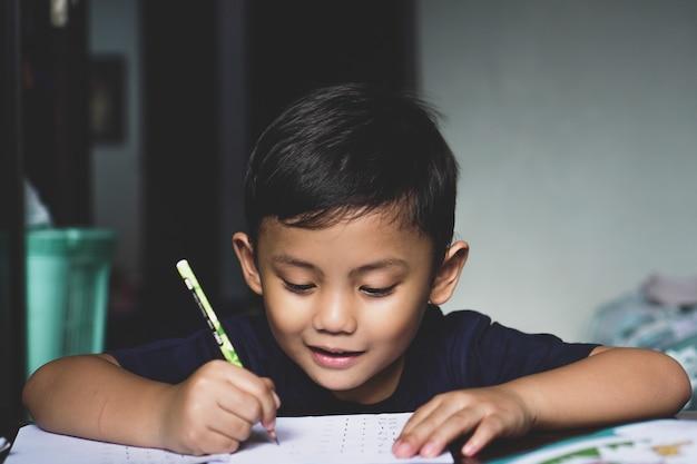 Der asiatische junge, der mit seinem studiengerät hinter dem schreibtisch sitzt, sieht man mit einem lächeln schreiben