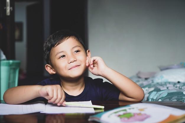 Der asiatische junge, der mit seinen lerngeräten hinter dem schreibtisch saß, lächelte und stellte sich etwas glückliches vor