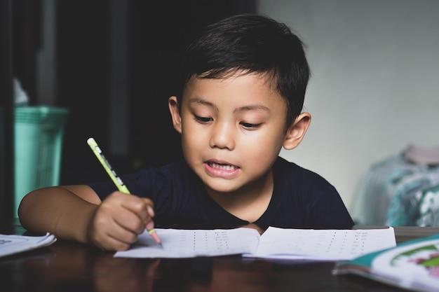 Der asiatische junge, der mit seiner lernausrüstung hinter dem schreibtisch sitzt, wird selbstbewusst beim schreiben gesehen