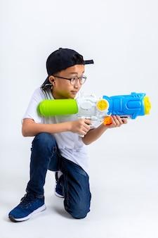 Der asiatische junge mit spritzpistole auf weißem hintergrund