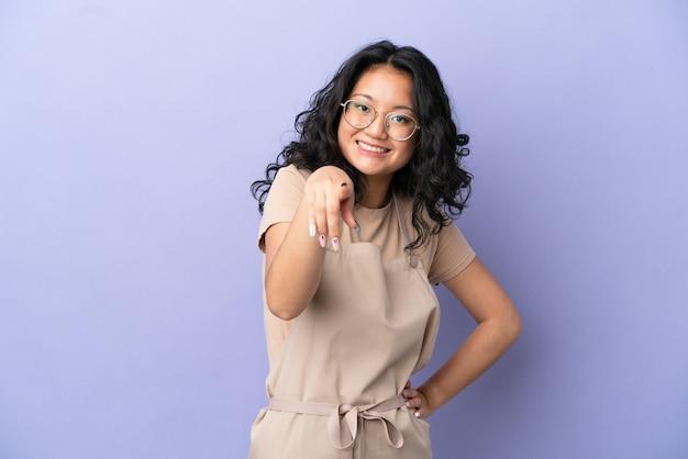 Der asiatische kellner des restaurants, der auf violettem hintergrund isoliert ist, zeigt mit einem selbstbewussten ausdruck mit dem finger auf sie