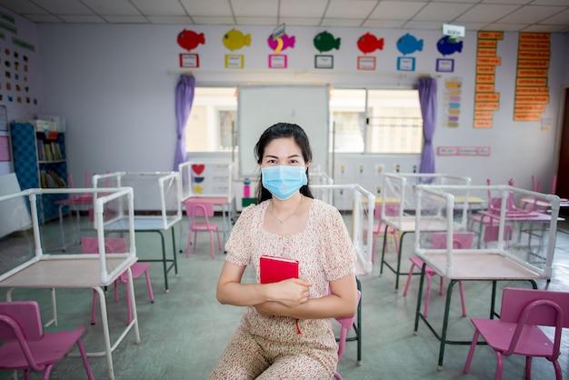Der asiatische lehrer trägt eine maske im klassenzimmer und in der schule, die kurz vor dem start steht
