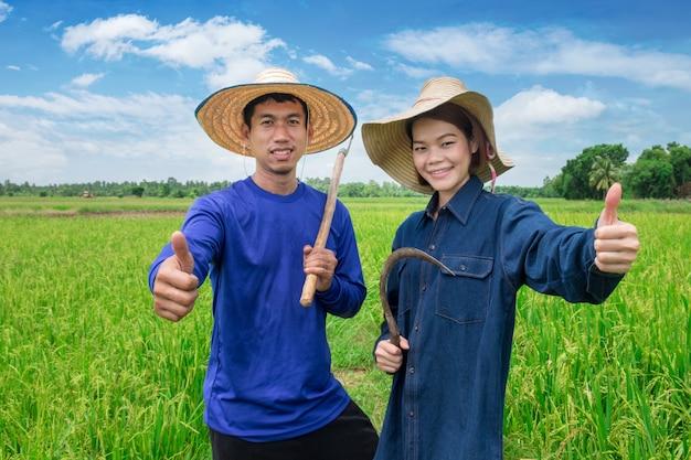 Der asiatische männliche und weibliche landwirt in der blauen landwirtuniform trägt einen hut, hält das gerät und hält den daumen mit einem lächeln auf dem grünen feld des himmels. mit guten produktionsergebnissen