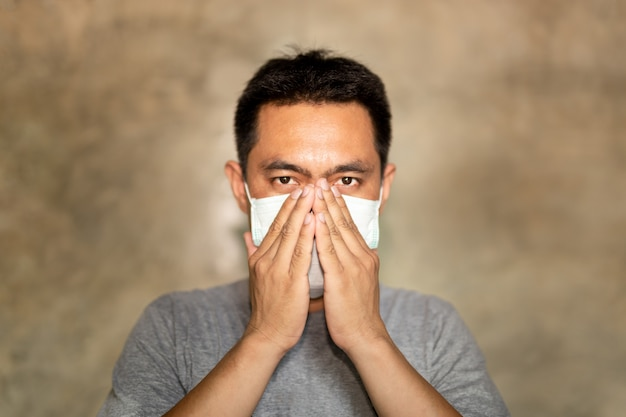 Der asiatische mann, der eine gesichtsmaske mit der hand trägt, bedecken seinen mund beim husten.