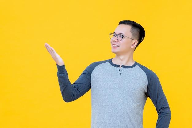 Der asiatische mann, der geste mit der hand darstellend tut, öffnet sich, um raum zu leeren