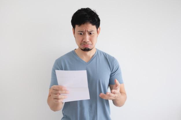 Der asiatische mann ist traurig und schockiert über den brief in seiner hand auf isoliertem hintergrund.
