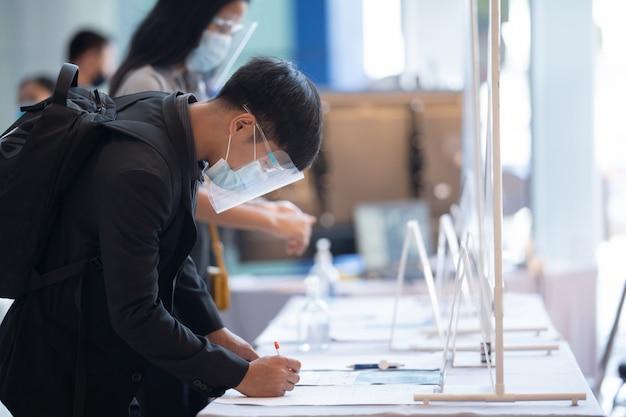 Der asiatische mann meldet einen test für covid 19 an, bevor er das kaufhaus betritt.