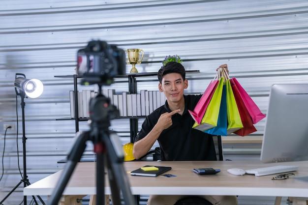 Der asiatische mann präsentiert dem online-markt ein produkt