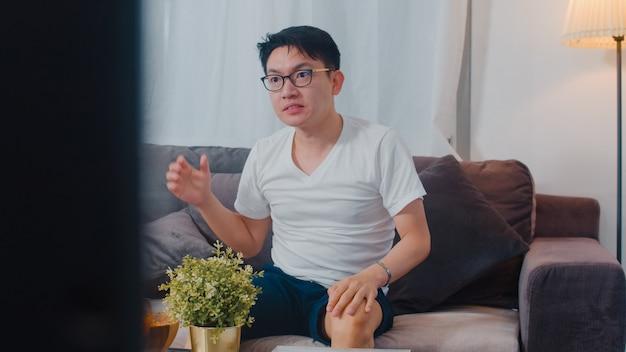 Der asiatische mann von mittlerem alter, der freizeit genießt, entspannen sich zu hause. jubelnder fußballsport der glücklichen spaßuhr des lebensstilkerls und uhrunterhaltung im wohnzimmer im modernen haus nachts.