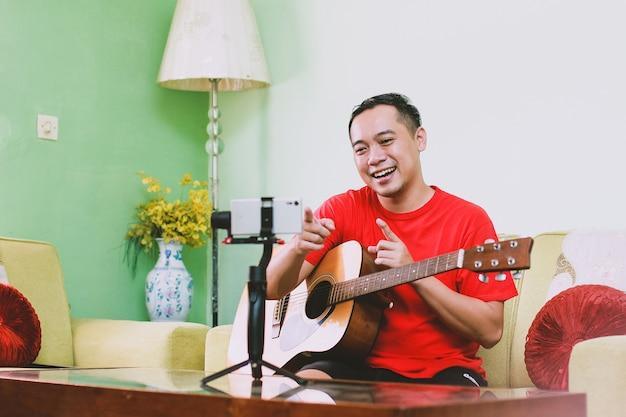 Der asiatische mann youtuber macht sich mit einer gitarre zufrieden und zeigt mit dem finger auf das publikum