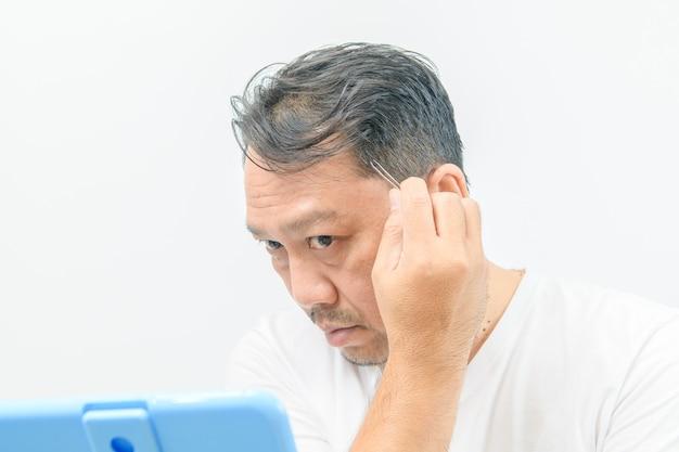 Der asiatische mittelsmann schaut in den spiegel und zupft mit einer pinzette an seinen grauen haaren