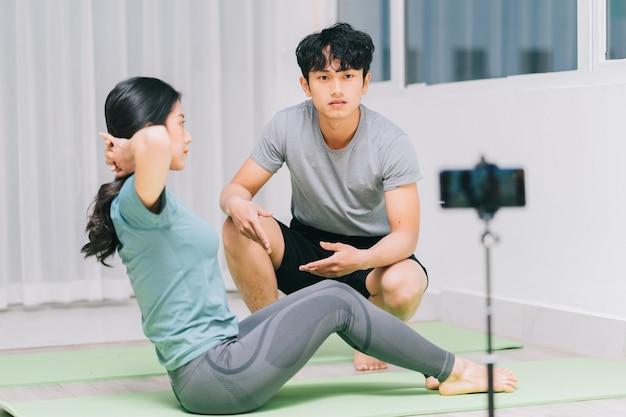 Der asiatische personal trainer führt die schüler zu yoga und videoaufnahmen, um yoga online zu unterrichten