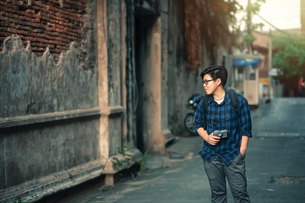 Der asiatische reisende, der das blaue karierte hemd trägt, das geht, mit film-kamera herein zu reisen, entspannen sich lifest