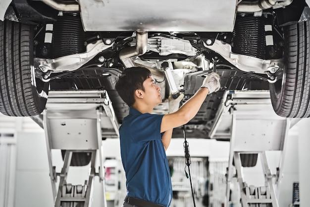 Der asiatische reparierende mechaniker und leuchten unter dem auto im wartungsservice-center
