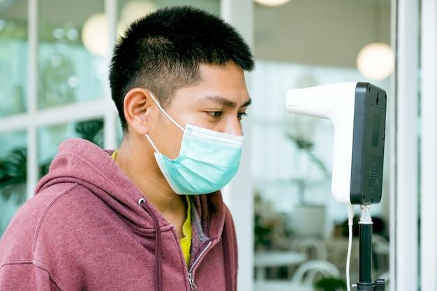Der asiatische touristenmann hat die körpertemperatur mit einem thermischen temperaturscanner-detektor, einem neuen normal- und reisesicherheitskonzept überprüft.