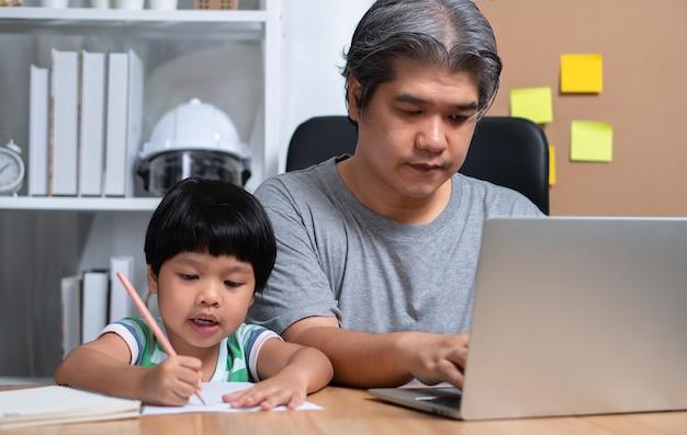 Der asiatische vater arbeitet zu hause mit einer tochter und lernt gemeinsam online-lernen von der schule