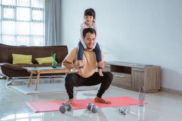 Der asiatische vater benutzt sein kind als gewicht, um zu hause sport zu treiben. mann macht kniebeugen, während er seine tochter trägt