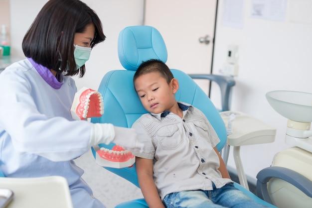 Der asiatische weibliche zahnarzt, der erklärt, wie man zahnjungen putzt, hören.