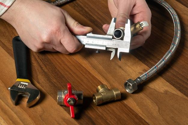 Der assistent misst die größe der armatur mit einem messschieber, bevor eine wasser- oder gasleitung angeschlossen wird. nahaufnahme der hände des meisters
