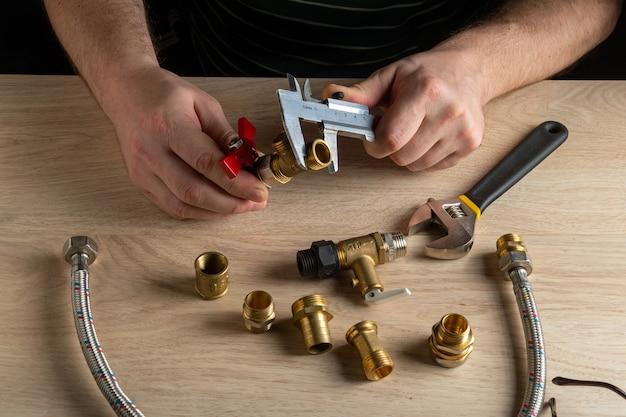 Der assistent misst die größe der armatur mit einem messschieber, bevor eine wasser- oder gasleitung angeschlossen wird.