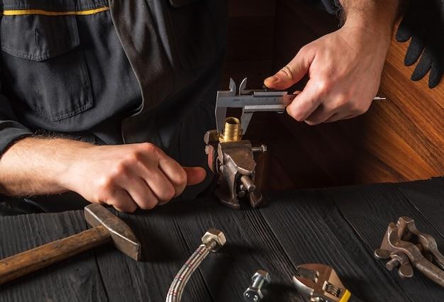 Der assistent misst die größe der armatur mit einem messschieber, bevor eine wasser- oder gasleitung angeschlossen wird