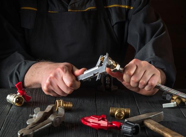Der assistent misst die größe der armatur mit einem messschieber, bevor er die wasser- oder gasleitung anschließt